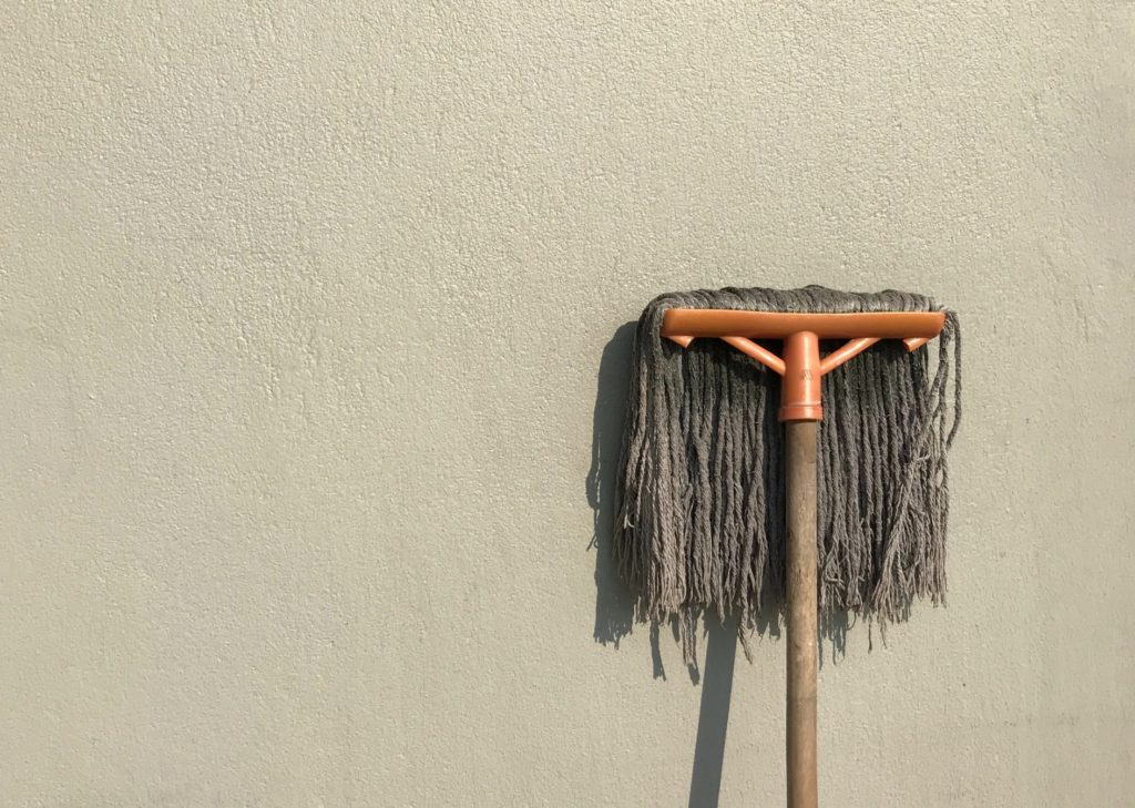 mop leaning against a beige wall