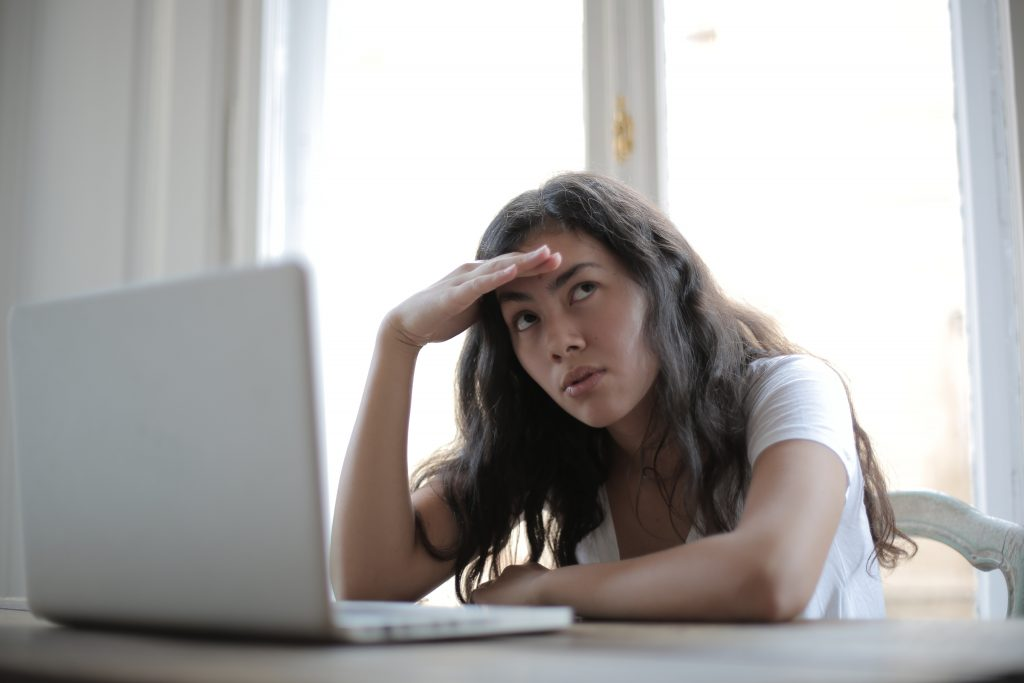 woman at laptop with hand on forehead thinking